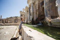 妇女旅行家做飞溅水在古老喷泉  免版税库存照片