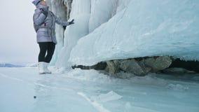 妇女旅行贝加尔湖冰的  旅行到冬天海岛 女孩走在冰岩石的脚 旅客看 影视素材