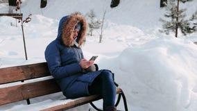 妇女日间坐长凳和浏览手机在冬天公园在城市多雪的天气的与 股票录像