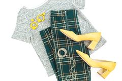 妇女时尚布料和辅助部件 与黄色鞋子、耳环、方格毛线衣和的裤子的女性背景 平的位置,上面竞争 免版税库存图片