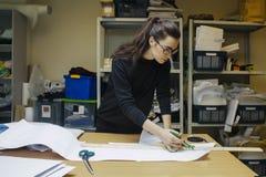 妇女时装设计师在地道车间内部的工作 免版税库存图片