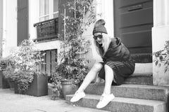 妇女时髦的成套装备坐台阶在入口房子美丽如画的街道附近在巴黎 叫作时尚的资本的巴黎 库存照片