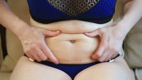 妇女是一个肥胖胃 超重和减重概念 游泳衣的一个女孩拉扯在她的胃的皮肤 影视素材
