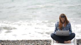 妇女是偶然坐和工作海滩清早 影视素材