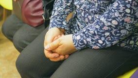妇女是和保持她的手联合坐她的腿 E 股票视频