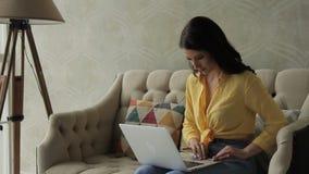 妇女是在有银色膝上型计算机的沙发在膝部,并且类型发短信,轻拍在键盘然后采取银行卡并且进入个人 股票录像