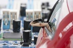 妇女是在汽车选择的焦点的方向盘的手使用现代技术拼贴画的概念 库存图片