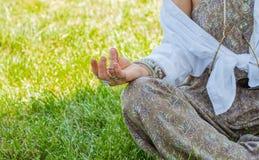 妇女是在莲花姿势的思考的开会在草在公园 与辅助部件、圆环和镯子的Boho样式 库存图片
