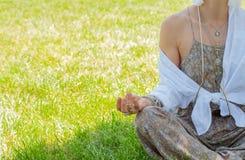 妇女是在莲花姿势的思考的开会在草在公园 与辅助部件、圆环和镯子的Boho样式 库存照片