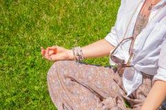 妇女是在莲花姿势的思考的开会在草在公园 与辅助部件、圆环和镯子的Boho样式 图库摄影