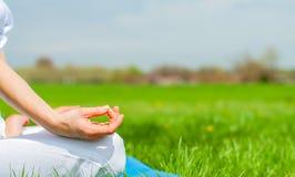 妇女是在莲花姿势的思考的开会在草在公园 库存图片