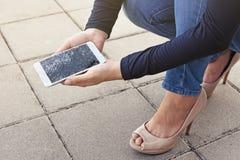妇女是坐和拿着一个残破的巧妙的电话 库存照片