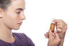 妇女是审查一个瓶同种疗法药物 库存图片