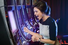 妇女是愉快的她的在老虎机的胜利 免版税库存图片
