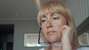 妇女是看屏幕的商人 女孩穿戴在眼睛的玻璃紧密  工作在办公室  股票录像