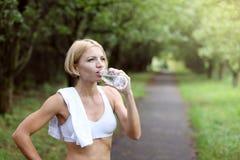 妇女是饮用水在体育运动以后 图库摄影
