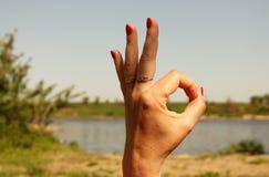 妇女显示好标志姿态的` s手,反对背景  免版税库存图片