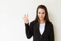 妇女显示4个或四个手指手势的商业主管 库存照片