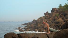 妇女显示urdhva在海岸慢动作的mukha shvanasana 股票视频