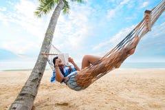 妇女晒日光浴放松和读书在吊床 库存图片