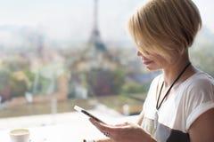 妇女智能手机巴黎咖啡馆 库存照片