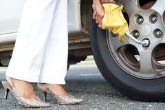 妇女更改的汽车轮胎 图库摄影