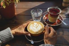 妇女有一杯咖啡的` s手特写镜头蛋糕,太阳` s光芒通过在咖啡馆的一个窗口发光 杯子现有量 库存图片