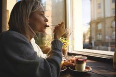 妇女有一杯咖啡的` s手特写镜头蛋糕,太阳` s光芒通过在咖啡馆的一个窗口发光 杯子现有量 免版税库存照片