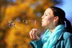 妇女有乐趣吹的泡影在秋季公园 免版税库存照片