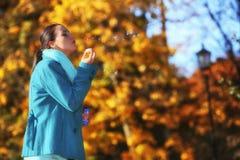 妇女有乐趣吹的泡影在秋季公园 图库摄影