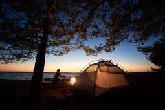 妇女有休息在野营在旅游帐篷,在海岸的营火附近的晚上在满天星斗的天空下 库存照片
