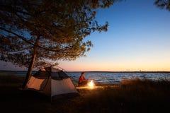 妇女有休息在野营在旅游帐篷,在海岸的营火附近的晚上在满天星斗的天空下 免版税库存照片