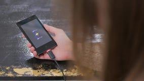 妇女有低电池象的举行智能手机在屏幕上 库存照片