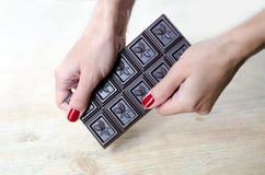 妇女有修指甲的` s手拿着一个整个巧克力 木背景 巧克力天 免版税库存图片