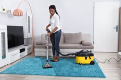 妇女有吸尘器的清洁地毯 库存照片