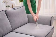 妇女有吸尘器的清洁长沙发 图库摄影