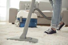 妇女有吸尘器的清洁地毯在屋子里 库存图片