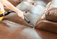妇女有吸尘器的清洁沙发 库存图片