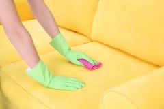 妇女有喷粉器的清洁长沙发 库存图片