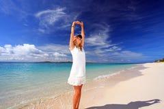 妇女有在海滩的舒展。 免版税库存图片