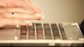 妇女有好的钉子的` s手在膝部上面的键盘键入 影视素材