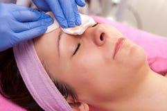 妇女有干净她的面孔在美容院 免版税库存图片