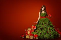 妇女有当前礼物的, Xmas时尚褂子圣诞树礼服 免版税图库摄影