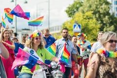 妇女有彩虹旗子的骑马摩托车在斯德哥尔摩骄傲游行期间的人群 库存照片