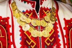 妇女有手被绣的五颜六色的` s女衬衫装饰与金币项链  免版税库存照片