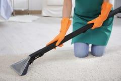 妇女有擦净剂的清洁地毯 免版税库存图片