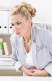 妇女有月经痛苦在办公室。 免版税图库摄影