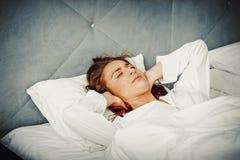 妇女有枕头的覆盖物耳朵由于噪声 库存照片