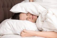 妇女有枕头的覆盖物头由于噪声 免版税库存图片