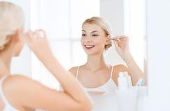 妇女有棉花棒的清洁耳朵在卫生间 免版税库存图片